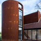 Башня обшитая листовым железом и такая же ржавая как и отделка других фасадов пристройки.