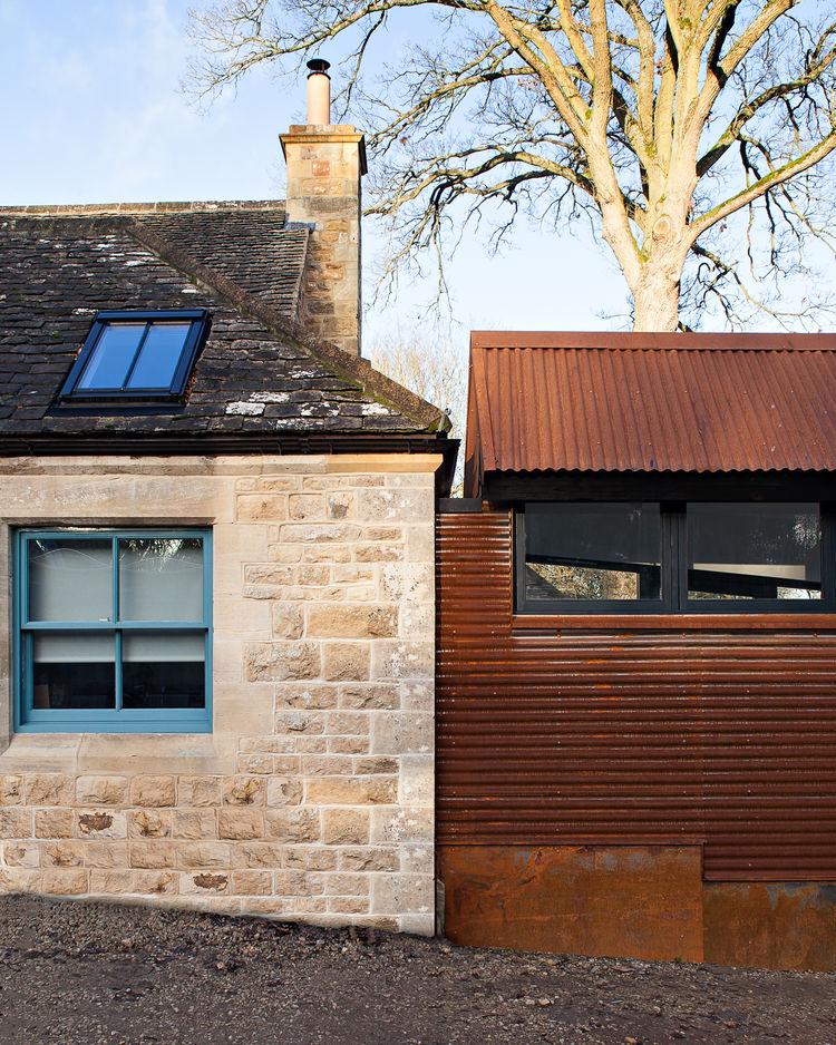 Контраст старого каменного строения и современной пристройки выполненной стиле лофт.