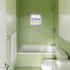 Окно в зеленой ванной выглядит как картина.