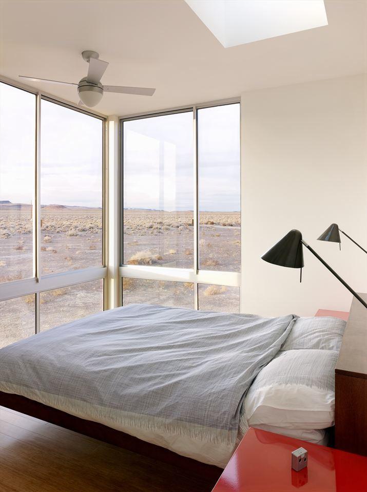 Одна из спален дома с угловым окном и потрясающим видом на пустыню.
