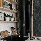 Дерево кухонных полочек и рамки доски смягчают черно-белую палитру кухни.
