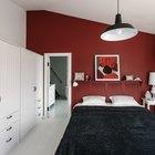 В спальне бордовая акцентная стена подчеркивает наклонный потолок добавляя спальне романтики. (спальня,эклектика,квартиры,аппартаменты,маленький дом,архитектура,дизайн,интерьер,экстерьер)