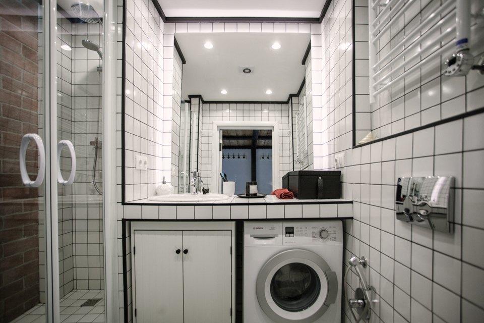 Дизайн ванной продолжает тему кухни, в частности использован тот же кафель. И, как и в кухне, столешница также отделана кафелем.