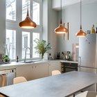Яркие светильники над обеденным столом оживляют серый интерьер кухни-столовой.