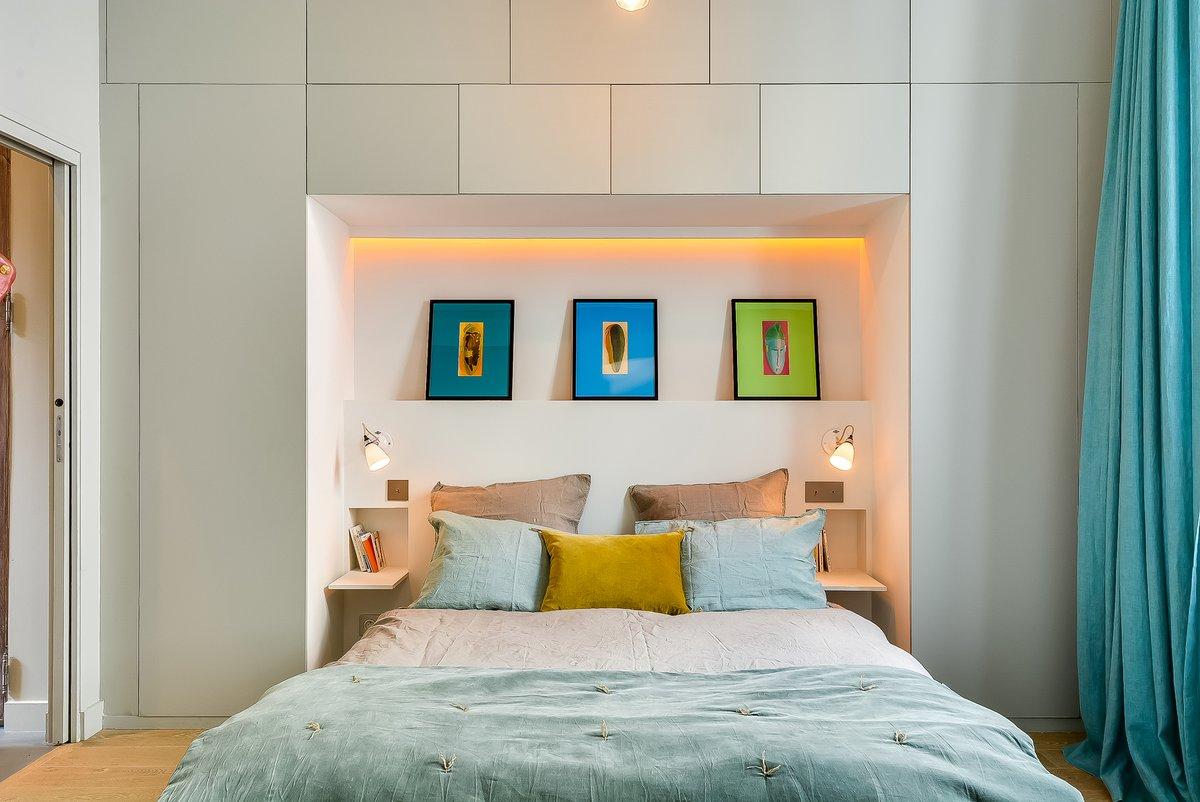 Изголовье кровати углублено в нишу образованную шкафом во всю стену. Сама ниша у изголовья кровати подсвечивается светодиодной подсветкой.