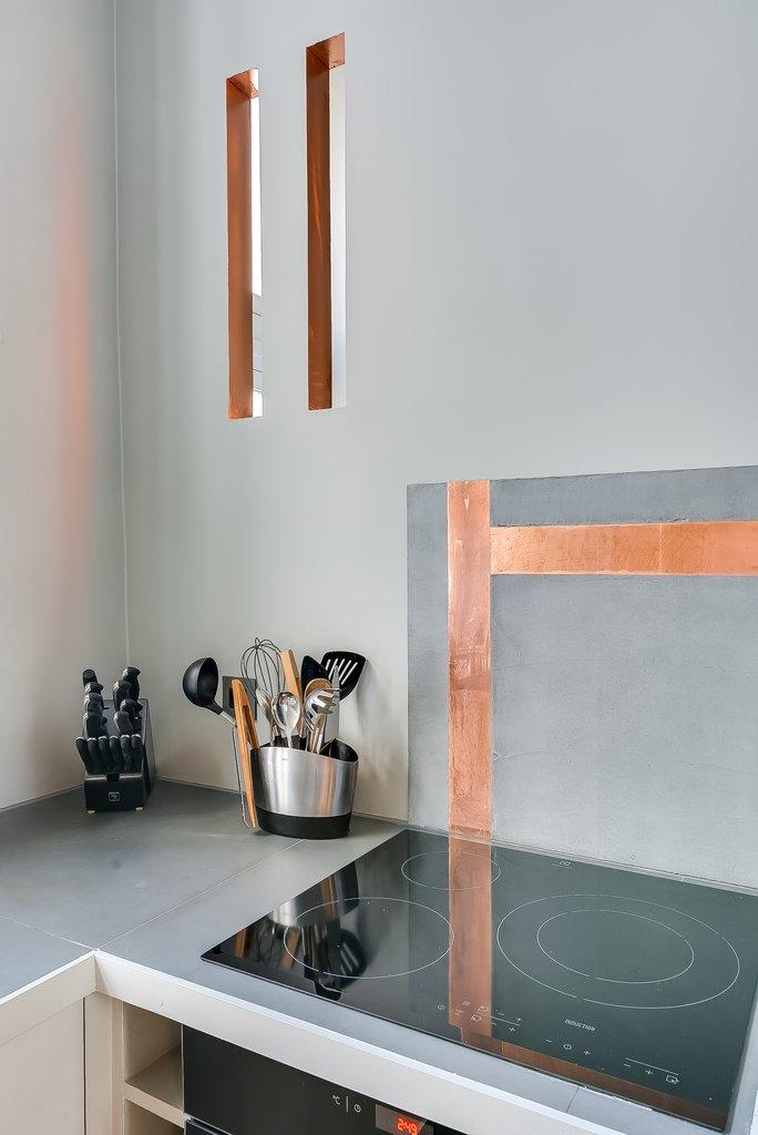 Небольшие вертикальные окошки над кухонной столешницей соединяют кухню с ванной комнатой.  Пропуская свет в обе стороны они украшают как кухню так и ванну