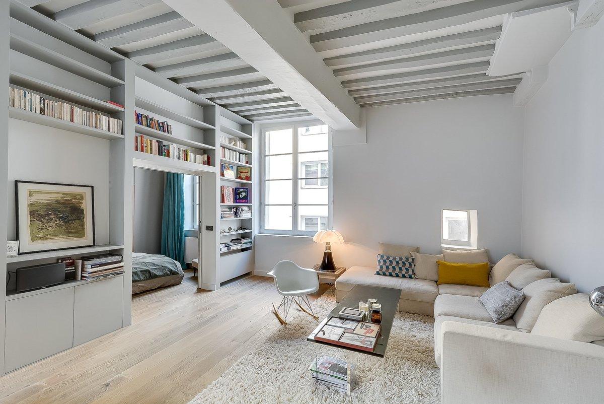 Спальня отделена от жилой комнаты книжными полками, а сами книги с обложками разных цветов украшают гостиную.