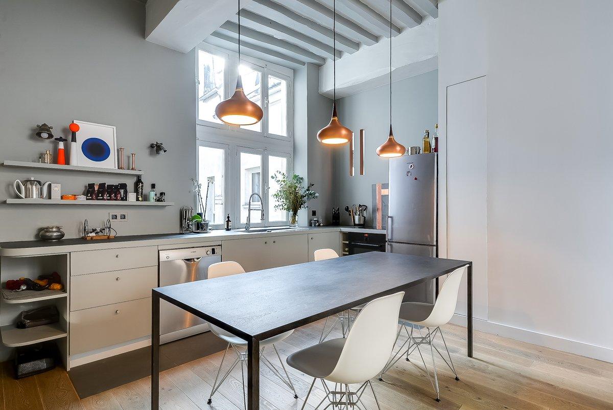 В центре кухни-столовой расположен стол с каркасом из профильной трубы. Стулья братьев Имз и светильники над столом делают интерьер столовой особенным и уютным. Особого внимания заслуживают светильники на стене над кухонной столешницей.