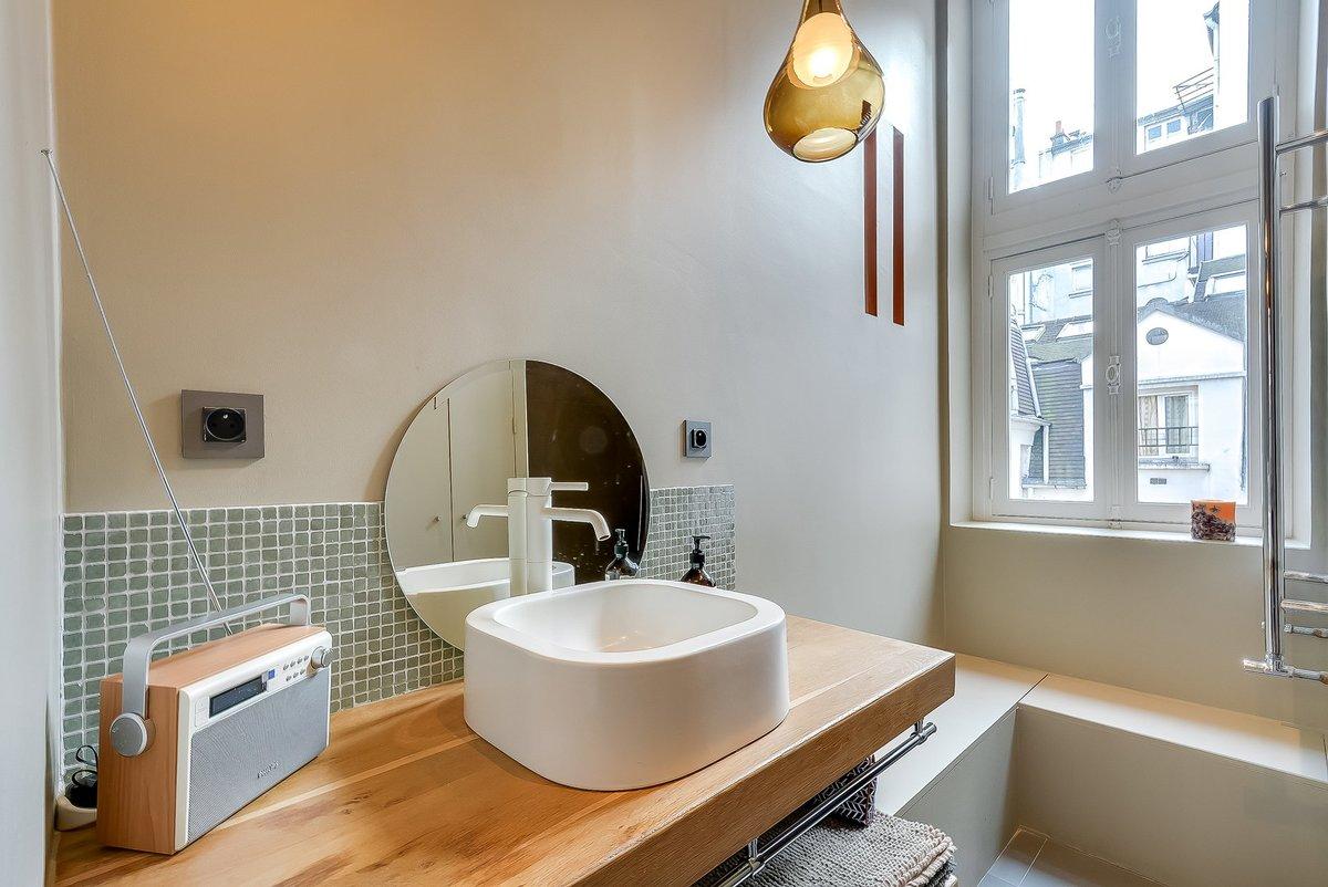 Великолепно выглядит толстая деревянная столешница под умывальником, а вот зеркало просится чтоб его повесили выше, либо нужно зеркало большего размера. На стене у окна видны узкие проемы соединяющие кухню и ванную комнату.