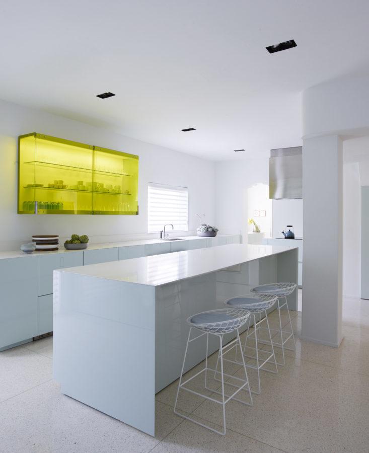Смелая кухня с сильным акцентом в виде верхнего шкафа остекленного желтым стеклом. Фото: Ричард Пауэрс