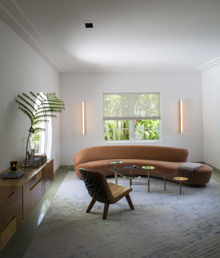 В гостиной отчетливо виден характер арт-деко, например большое круглое окно с видом на двор с бассейном. Однако владелец не хотел чтобы дом выглядел как типичный дом арт-деко в Майами, хотел создать приятный эклектичный интерьер. Фото: Ричард Пауэрс
