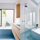 Окно из ванной первого этажа выходит на небольшой внутренний дворик между старым и новым домом. Это обеспечивает приватность, одновременно впуская природу и свет в дом.