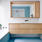 В ванне на первом этаже был использован голубой цвет, а мебель повторяет стиль другой мебели в доме. (архитектура,дизайн,экстерьер,интерьер,дизайн интерьера,мебель,современный,минимализм,ванна,санузел,душ,туалет,дизайн ванной,интерьер ванной,сантехника,кафель,керамика,фото ванной,идеи ванной)