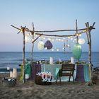 Гирлянды из фонариков, как и бумажные фонарики разных размеров задают необычное пляжное настроение.