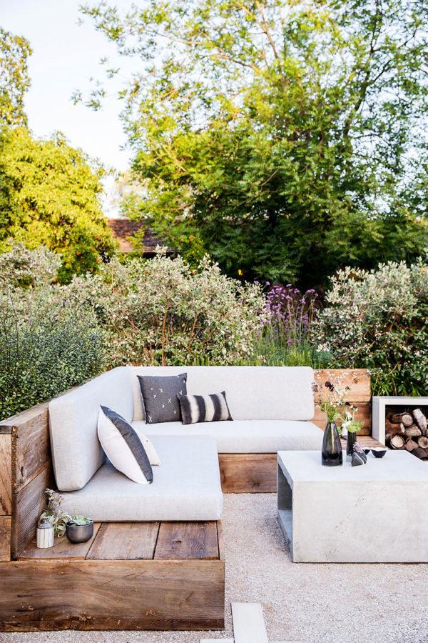 Уютный дворик с намеком на стиль лофт, на что намекает угловая деревянная скамья с мягкими подушками и бетонный журнальный столик.