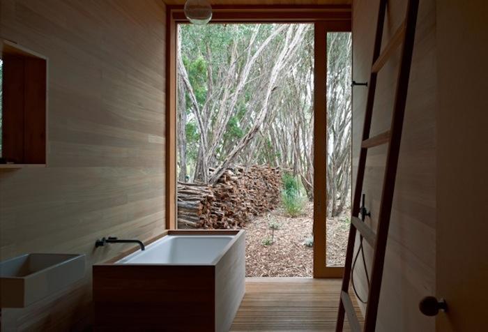 Деревянная отделка ванной комнаты подчеркивает связь с природой за большим размером во всю стену окном