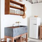 Массивная кухонная раковина является изюминкой кухни. В раковине размещается решетка из тикового дерева для сушки посуды, а над раковиной повесили полку для хранения посуды выполненную на заказ. (скандинавский,скандинавский интерьер,скандинавский стиль,архитектура,дизайн,экстерьер,интерьер,дизайн интерьера,мебель,кухня,дизайн кухни,интерьер кухни,кухонная мебель,мебель для кухни,фото кухни)