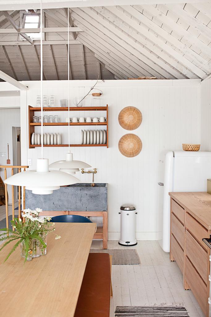 Белые стены и полы, высокие потолки и обилие деревянных текстур создают атмосферу скандинавского коттеджа.