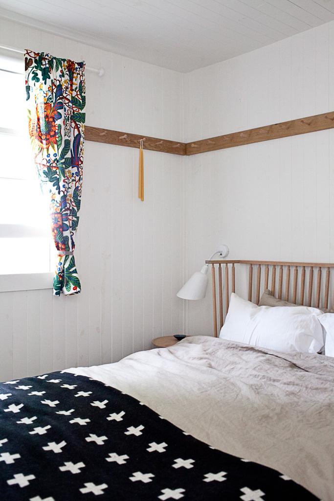 Изголовье кровати в родительской спальне повторяет дизайн спинки скамьи в столовой. Узор покрывала на кровати также выбран соответствовать скандинавскому стилю спальни.