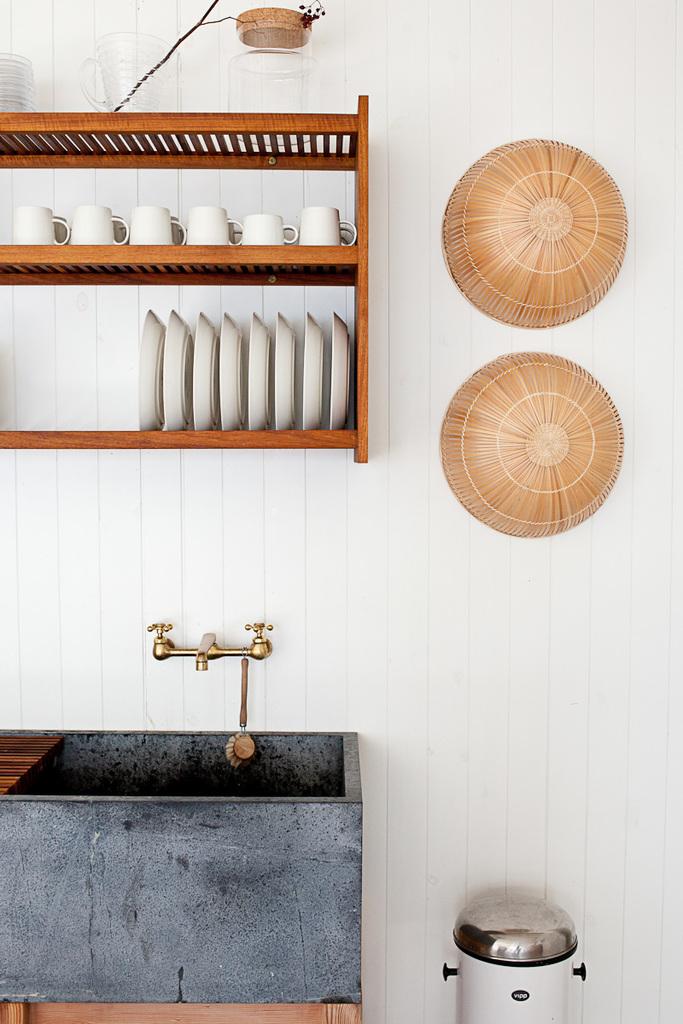 Латунный кран сочетается с другим латунным декором на кухне. Корзинки на стене от Икеа украшают натуральный экологичный интерьер.