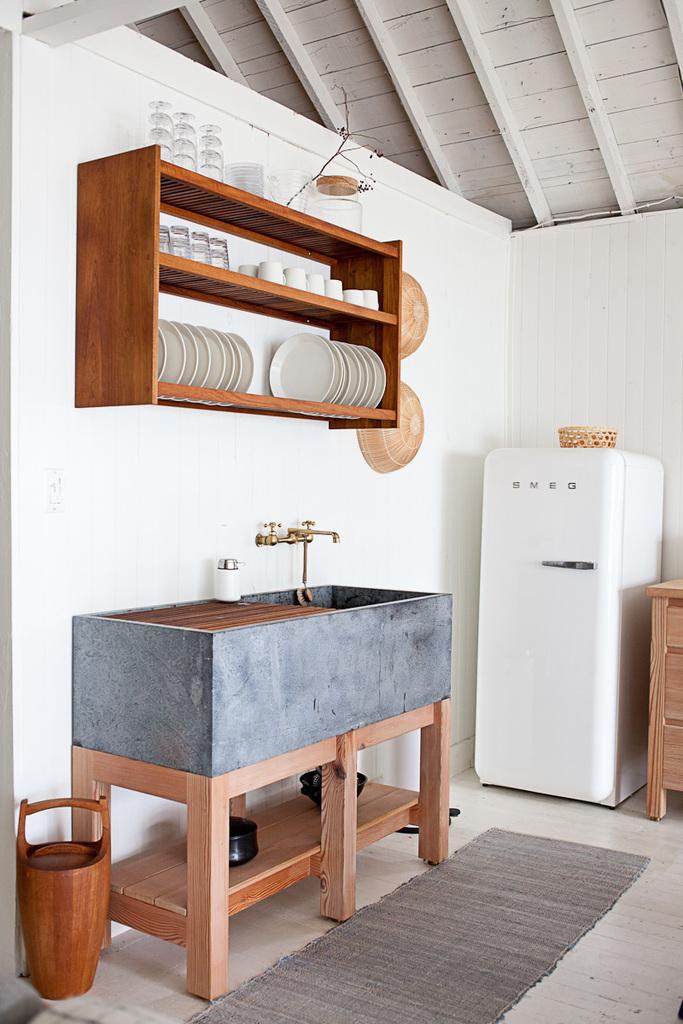 Массивная кухонная раковина является изюминкой кухни. В раковине размещается решетка из тикового дерева для сушки посуды, а над раковиной повесили полку для хранения посуды выполненную на заказ.