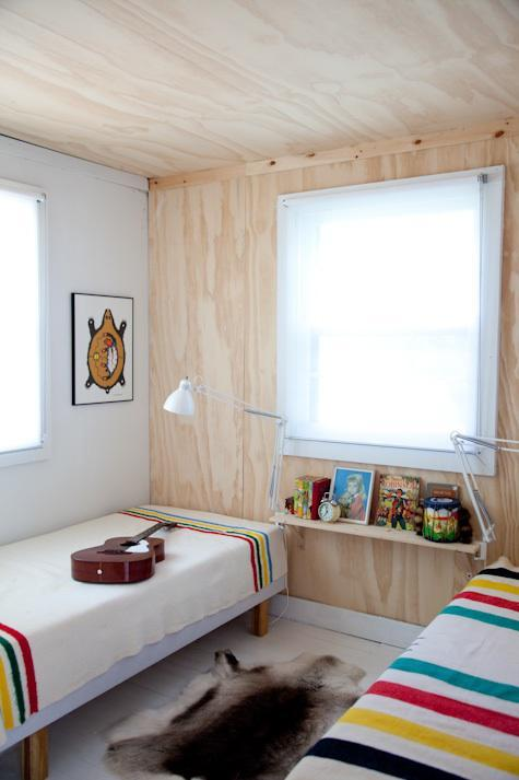 Небольшая, но светлая гостевая спальня. Фанерная обшивка одной из стен переходящая в фанерную обшивку потолка добавляют натуральности и экологичности скандинавскому интерьеру. Креативно использованы светильники закрепленные на полке под окном.