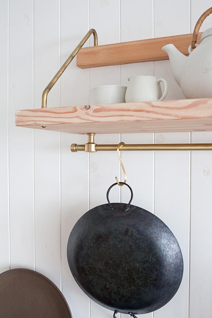 Пара хотела включить в интерьер кухни латунные детали, такие как этот латунный стержень с крючками на которые можно повесить посуду и кухонные принадлежности освободив место на столешницах.
