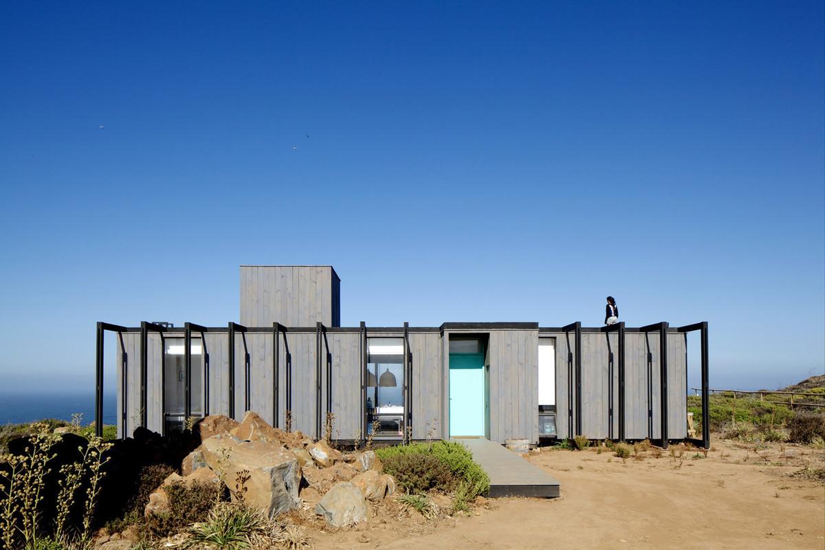 Внешний экзоскелет дома выделен черным цветом не фоне серого фасада. Он как бы обхватывает и защищает дом.