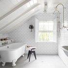 Белая ванная комната на мансарде с отдельно стоящей ванной и двумя душевыми лейками на противоположной стене. Элегантности ванной добавляют белые деревянные ставни на единственном окне. (ванна,санузел,душ,туалет,дизайн ванной,интерьер ванной,сантехника,кафель,керамика,фото ванной,идеи ванной,интерьер,дизайн интерьера,традиционный интерьер,традиционный стиль,мебель в традиционном стиле)