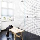 Великолепный двойной душ за стеклянной перегородкой. Белый кафель удачно контрастирует с черным кафелем елочкой на полу. Элегантную простоту интерьера подчеркивает деревянная скамья.