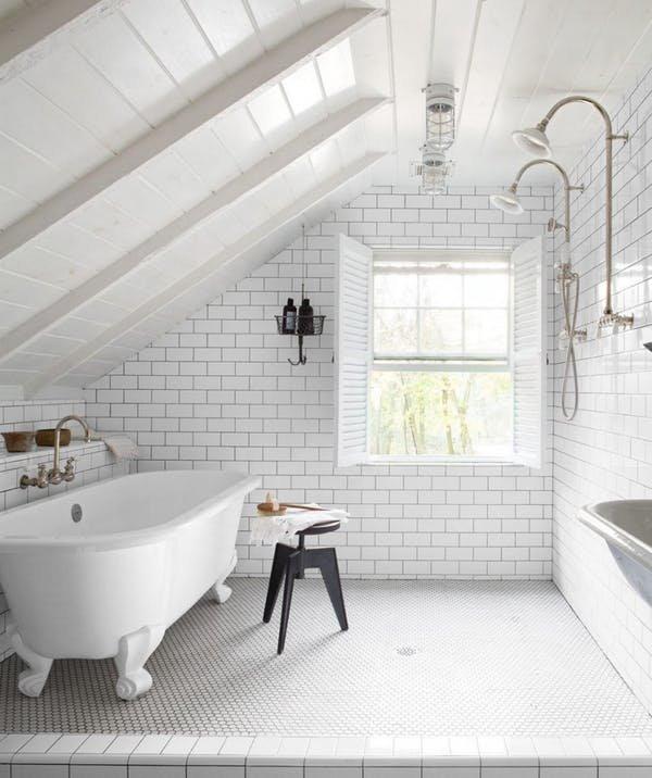 Белая ванная комната на мансарде с отдельно стоящей ванной и двумя душевыми лейками на противоположной стене. Элегантности ванной добавляют белые деревянные ставни на единственном окне.