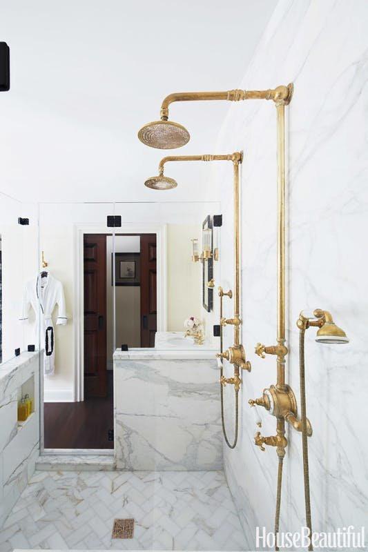 Ванная комната отделана белым мрамором. Светильники, вешалки и краны с душевыми лейками из латуни имитируют винтажный вид