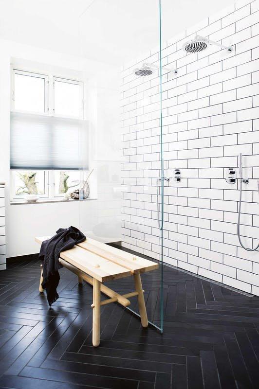 Великолепный двойной душ за стеклянной перегородкой. Белый кафель удачно контрастирует с черным кафелем елочкой на полу. Элегантную простоту интерьера подчеркивает деревянная скамья