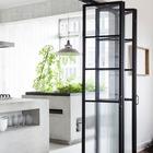 Очень массивный кухонный остров из бетона на кухне с огородом-оранжереей. Второй кухонный остров является грядкой. Бетон органично дополнен сдвижными дверьми-гармошкой из стекла и металла.