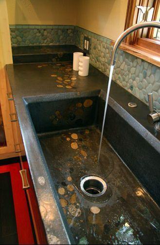 Черная бетонная кухонная столешница со встроенной бетонной кухонной раковиной.