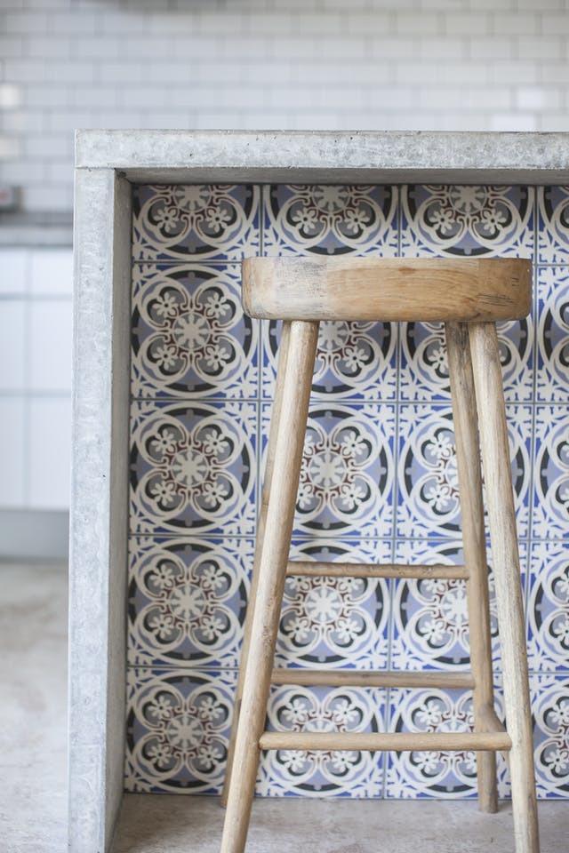 Холодное ощущение от интерьера в стиле лофт смягчается использованием декоративной кафельной плитки на фасаде барной стойки и деревянных барных стульев.