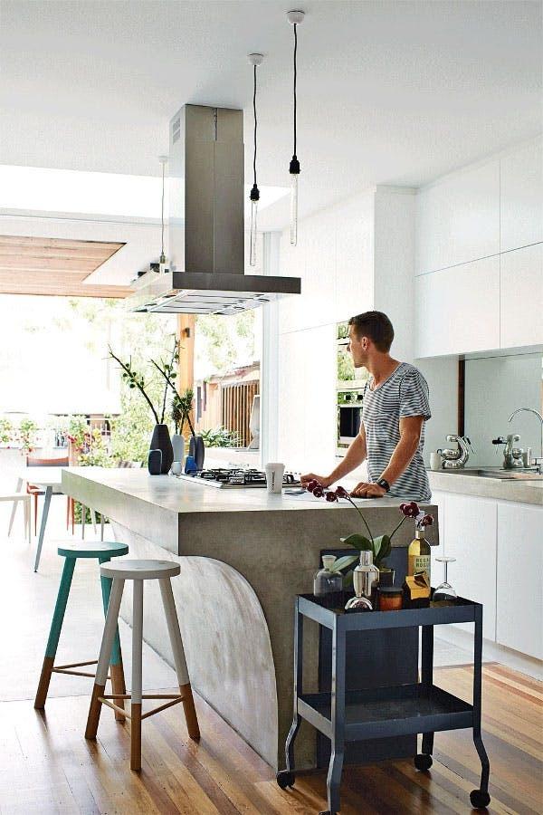 Массивная бетонная барная стойка одновременно служащая кухонным островом.
