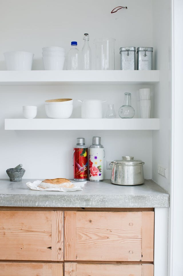 Минималистские белые полки дополняются светло-серой кухонной бетонной столешницей и выдвижными ящиками из повторно использованной древесины.