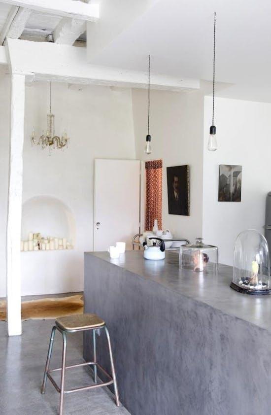 На этой кухне бетонный кухонный остров является продолжением бетонного пола из которого он вырастает.