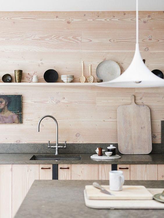 Теплые оттенки и текстуры дерева в отделке кухни оттеняются серым бетоном кухонных столешниц.