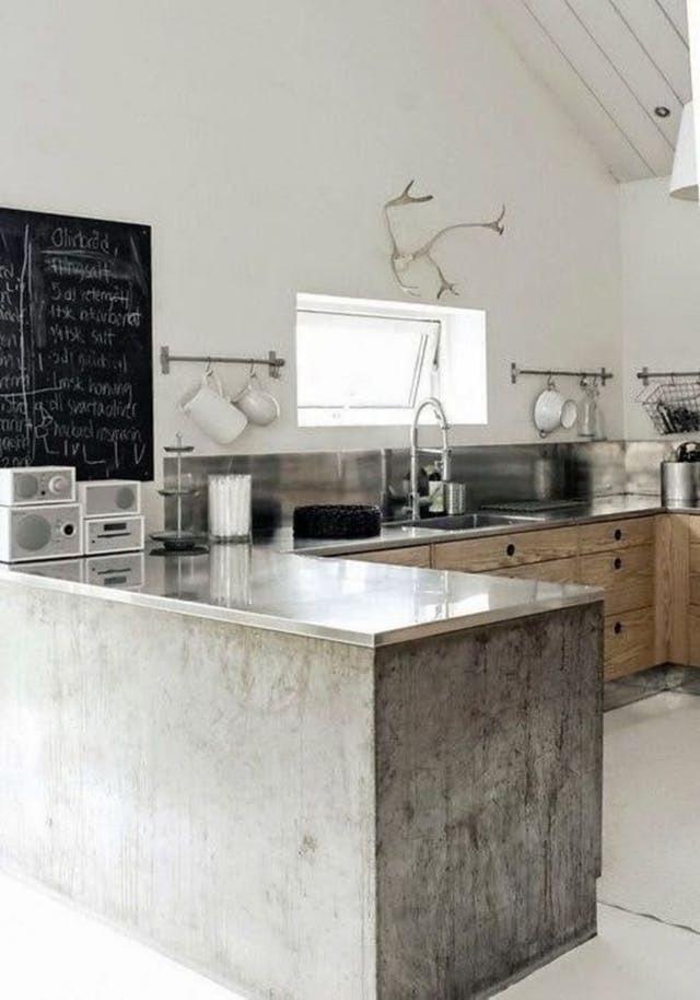 В данном случае дизайнер использовал столешницу из нержавейки на бетонном основании полуострова.