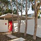 Вход в дом оформлен в лучших модернистских традициях. Яркие входные ворота четко разграничивают внешнее и внутреннее пространство дома, при этом окна под потолком обеспечивают связь