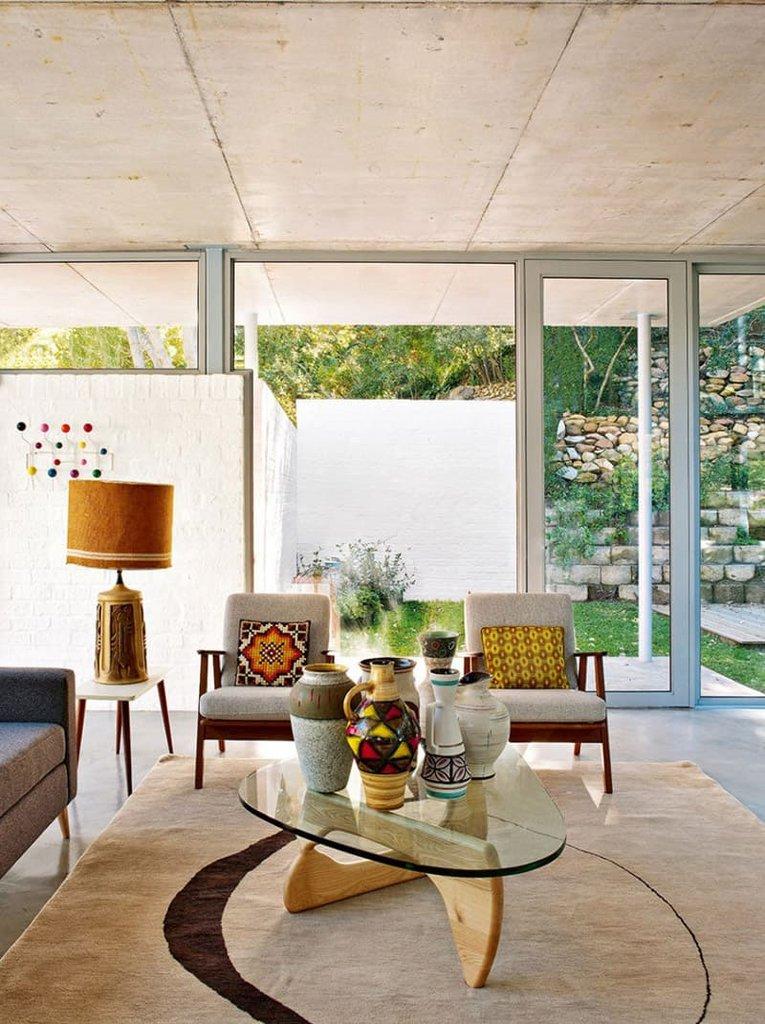 Центром гостиной является стеклянный столик Исаму Ногути с фарфоровыми вазами