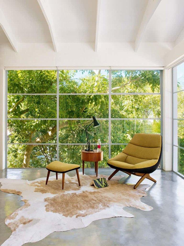 Идеальное место для того чтобы отдохнуть и почитать любимую книгу в удобном кресле. Шкура буйвола делает интерьер с бетонным полом значительно теплее.