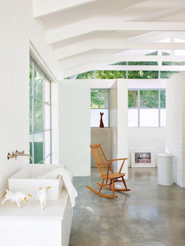 Минималистская ванна на втором этаже украшена фарфоровыми фигурками и постером стоящим прямо на полу. Кресло-качалка в центре ванной навевает расслабленное настроение.