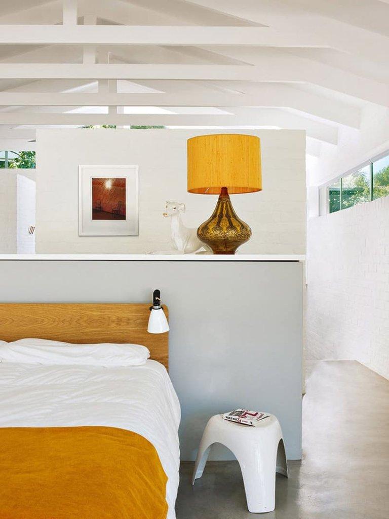 Одна из спален на втором этаже дома. В качестве прикроватных светильников использованы плафоны-прищепки на деревянном изголовье кровати. За не достигающей потолка белой кирпичной перегородкой находится ванна. Видно открытые стропильные конструкции и окна под самой крышей.