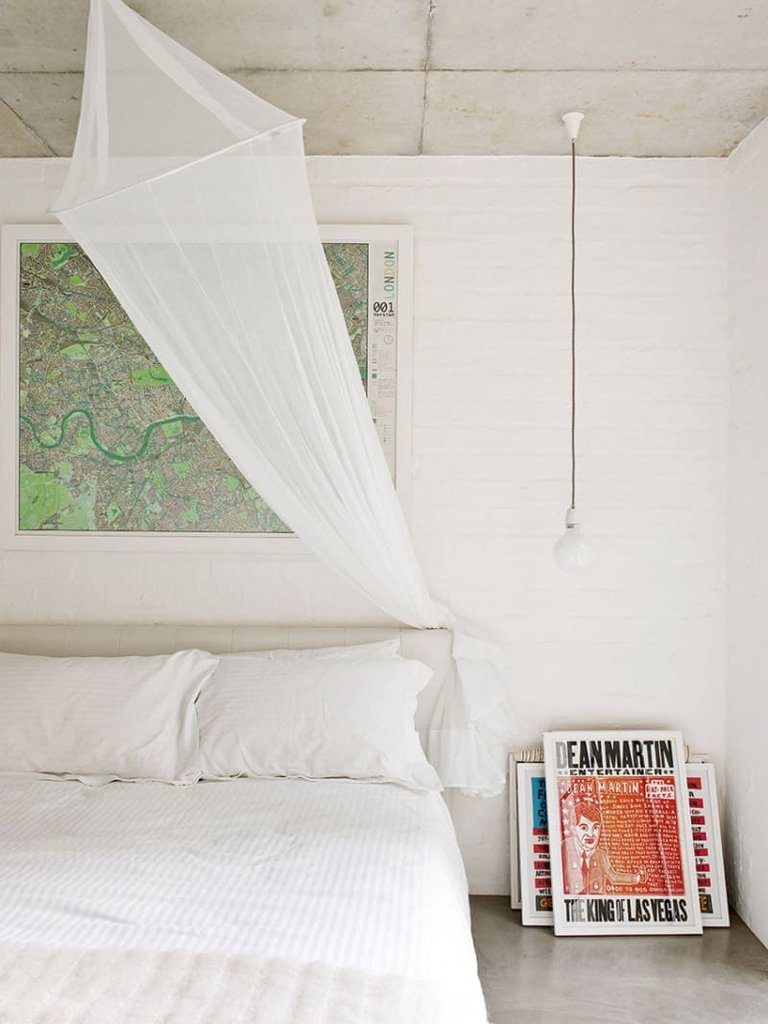 Спальня с окрашенными в белый цвет кирпичными стенами, картой города в изголовье и свисающими с потолка плафонами в качестве прикроватных светильников