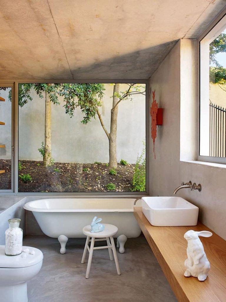 Ванная комната на первом этаже остается достаточно приватным помещением даже с большими окнами без занавесок, благодаря высокому глухому забору.