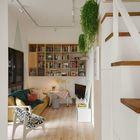 Стеллаж для книг на стене гостиной и небольшой рабочий столик под ним.