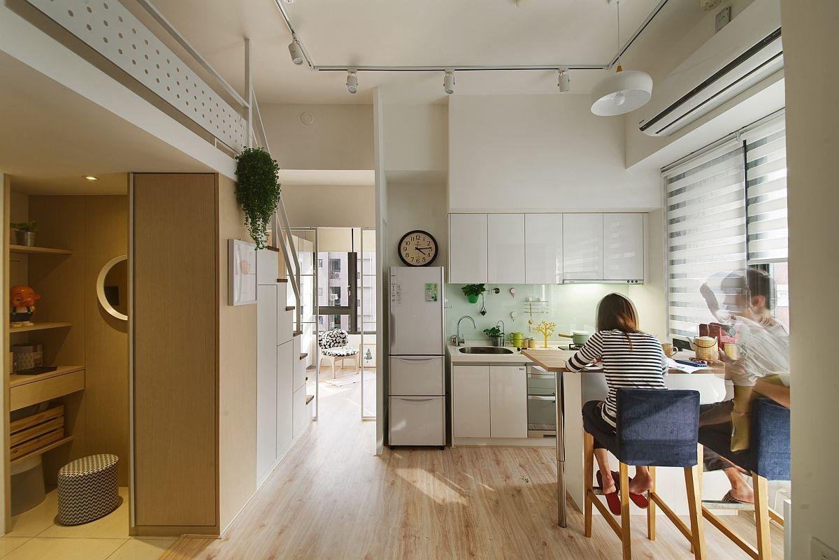 Белая кухня не отвлекает на себя внимания и почти теряется в пространстве. Небольшой барной стойки у окна вполне достаточно для городской квартиры.